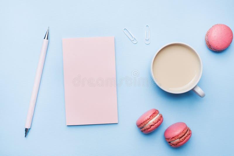 概念早晨早餐咖啡、蛋白杏仁饼干曲奇饼和笔记薄在蓝色淡色背景 r 免版税库存照片