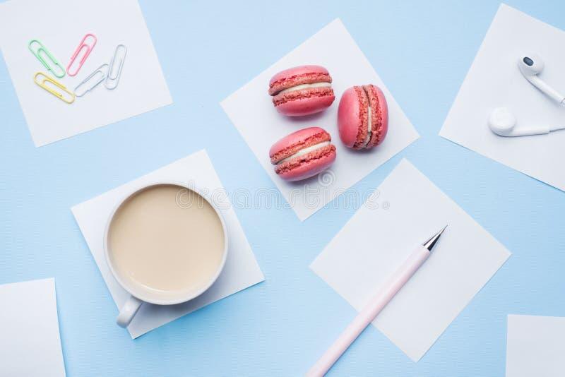 概念早晨早餐咖啡、蛋白杏仁饼干曲奇饼和笔记薄在蓝色淡色背景 r 库存图片