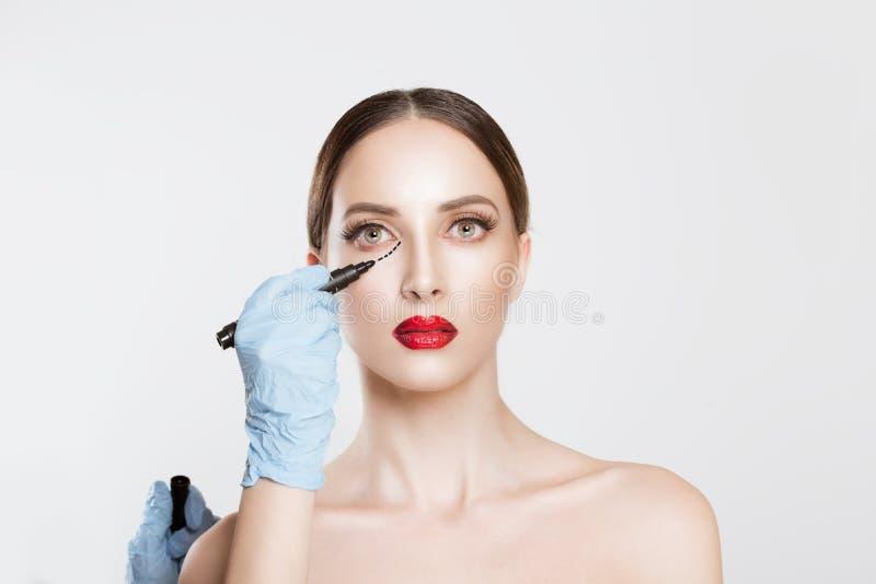 概念查出的整容手术白色 篡改Hands在女性面孔的图画标记反对白色灰色背景 面部治疗 画象是 免版税库存照片