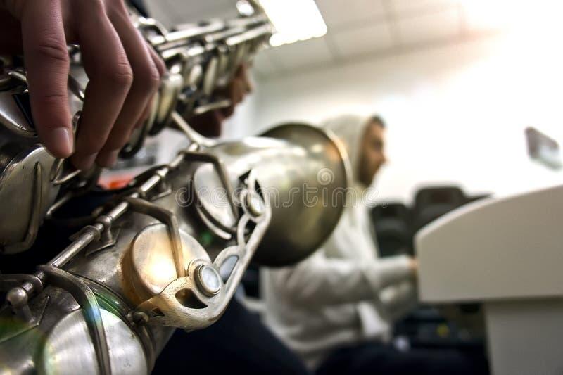 概念电吉他例证音乐 使用在萨克斯管的萨克管演奏员的手特写镜头反对白色 水平的图象 免版税库存图片