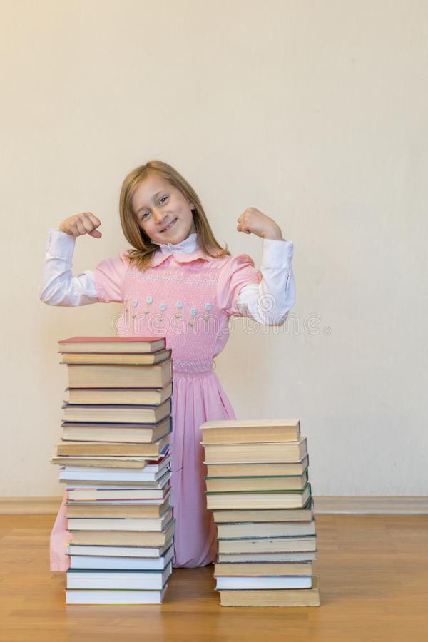 概念知识的力量 有堆的一个女孩书显示她的力量 r r r 免版税库存照片