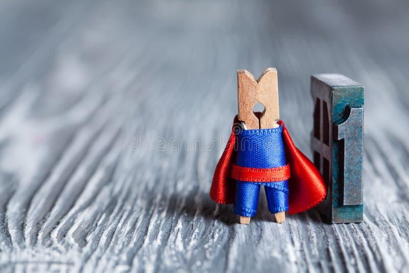 概念第一 晒衣夹超级英雄和1 (一个)写与色的葡萄酒活版 库存图片