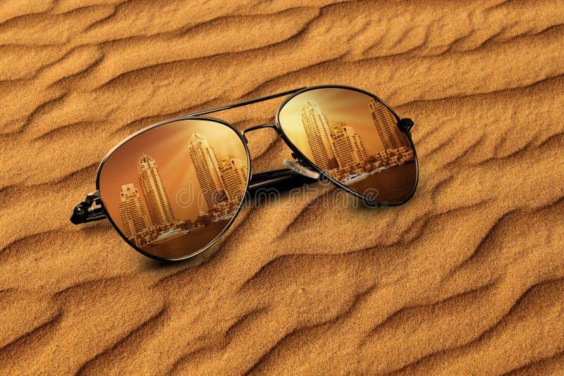 概念老迪拜沙子&新的迪拜反射在太阳镜 免版税库存图片