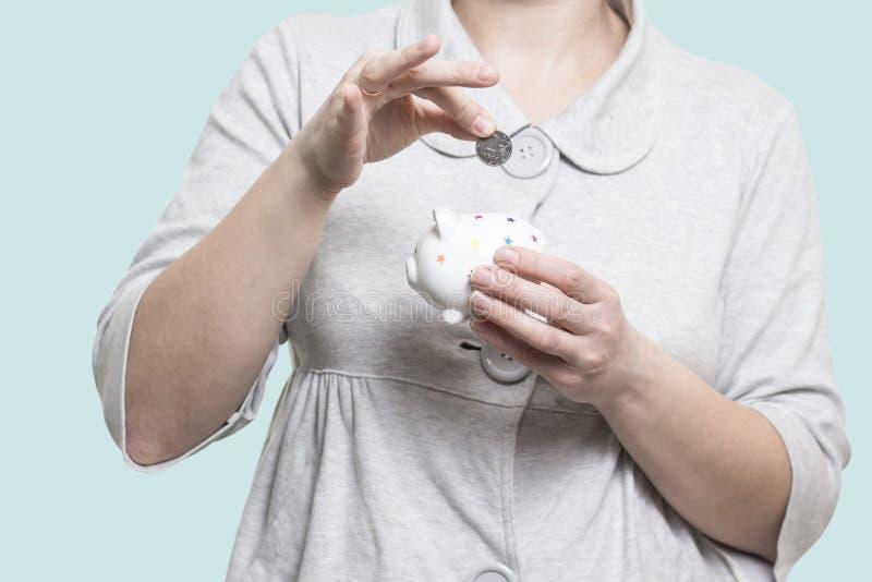 概念货币保存 女孩在存钱罐中投入硬币 保留货币 免版税库存照片