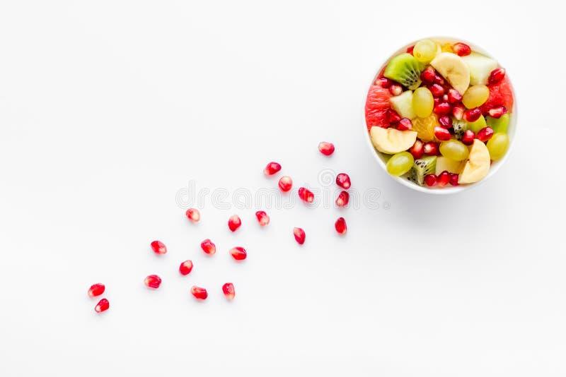 概念饮食果子查出的白色 水果沙拉用苹果、猕猴桃和石榴在碗在白色背景顶视图拷贝空间 免版税库存照片
