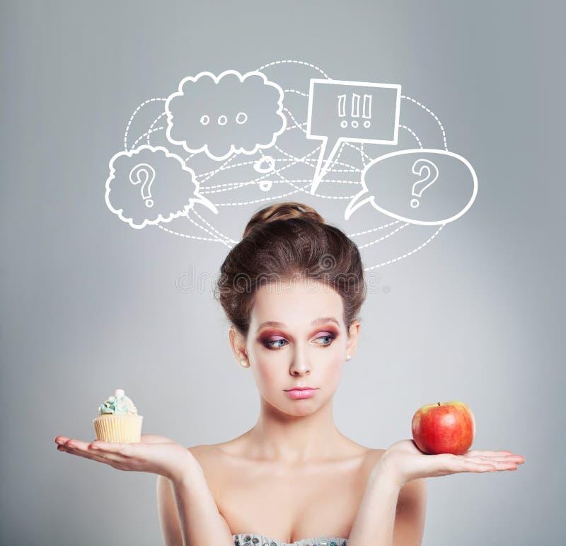 概念饮食 哀伤的妇女用健康和不健康的食物 库存照片
