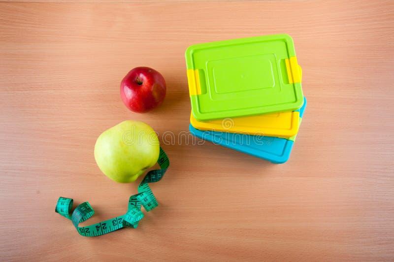 概念饮食 在苹果的顶视图,测量的磁带,在木背景的塑料午餐盒 库存图片