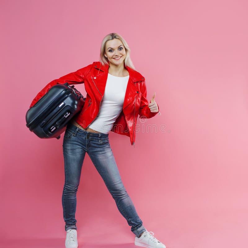概念,准备绊倒 带着旅行手提箱的少妇显示拇指 桃红色背景的白肤金发的旅游女孩 库存图片