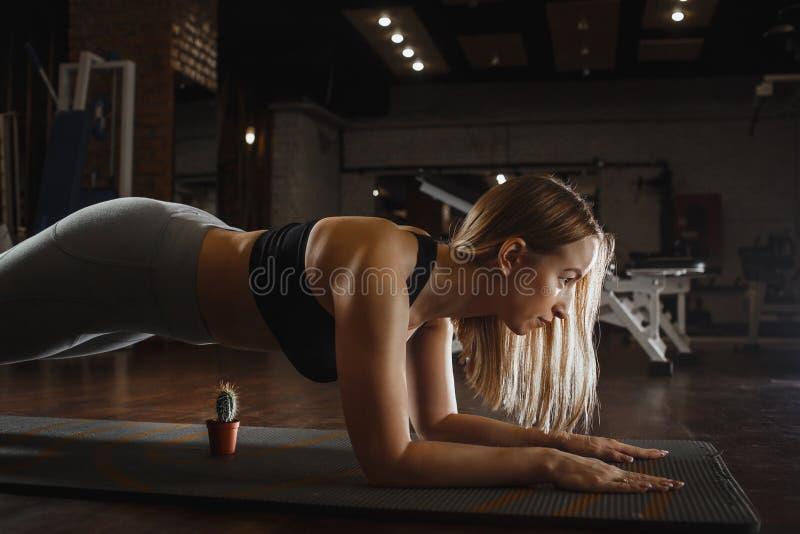 概念:刺激,自我克制力,力量,健康生活方式,体育 在板条的强有力的有吸引力的肌肉妇女立场 免版税库存照片