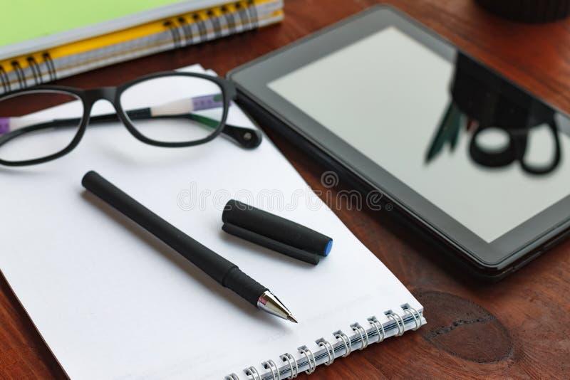 概念:工作起点  笔、开放笔记本、片剂计算机和玻璃在办公桌上 图库摄影