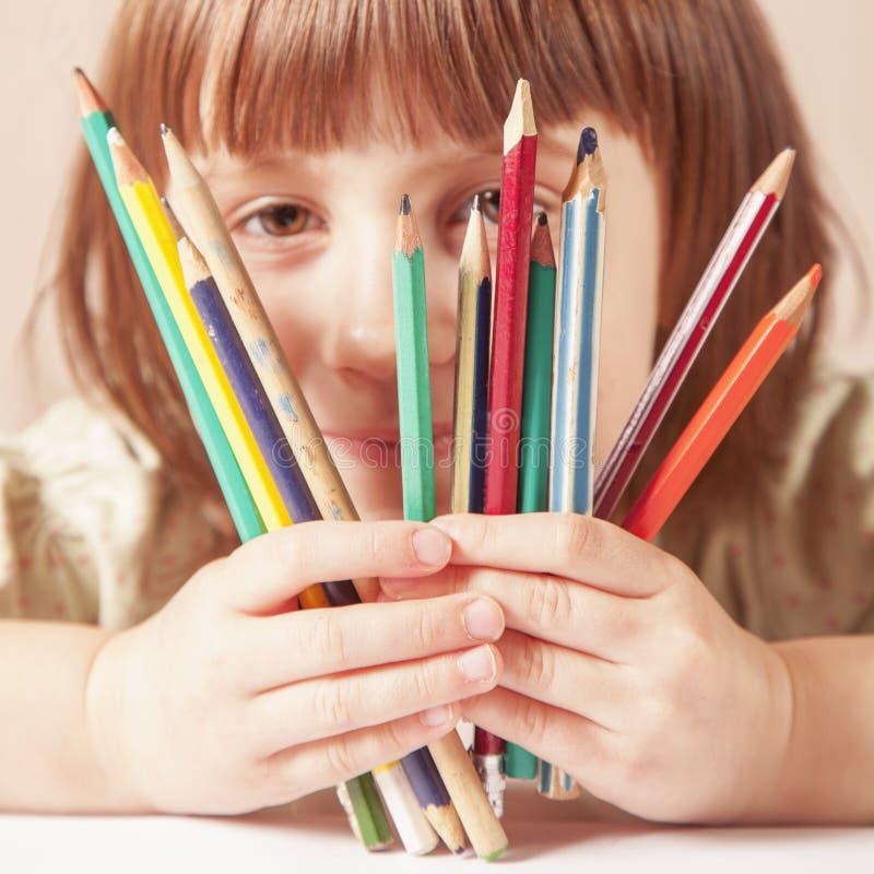 概念:生活是美好和五颜六色的 逗人喜爱的小孩女孩伟大的艺术家画象幽默照片有色的铅笔的 库存照片