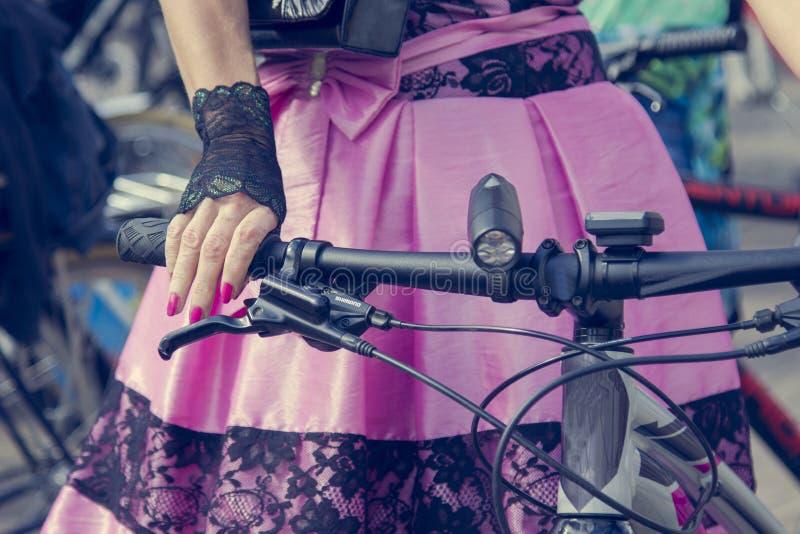 概念:自行车的妇女 拿着把手的手 有黑鞋带的桃红色裙子 免版税库存图片