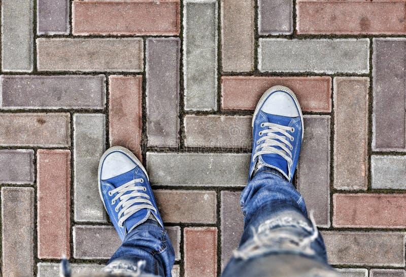 概念:道路的起点,方向选择  在视图之上 在蓝色运动鞋的腿在路面 选择, 库存图片
