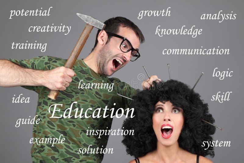 概念-教育,学会,家庭教师 投入信息在头 一个人锤击钉子入女孩的头 库存图片