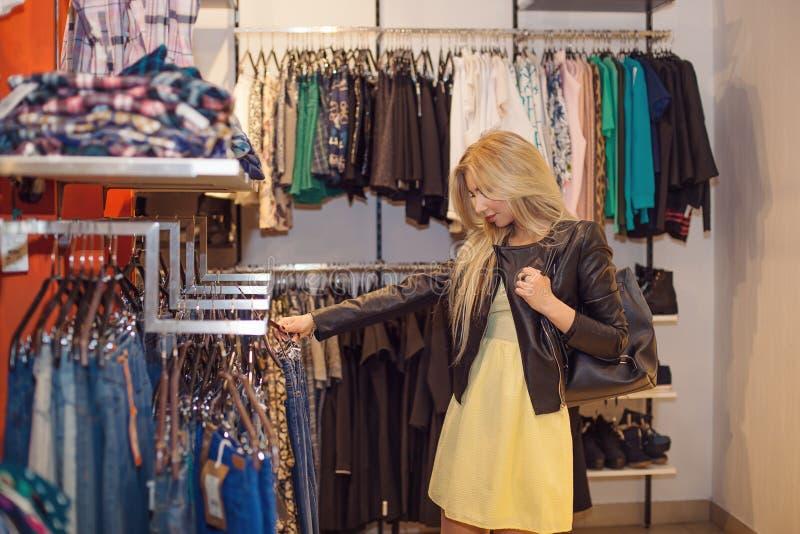概念购物 秀丽微笑的妇女画象在商店,选择穿衣 室内 免版税库存照片