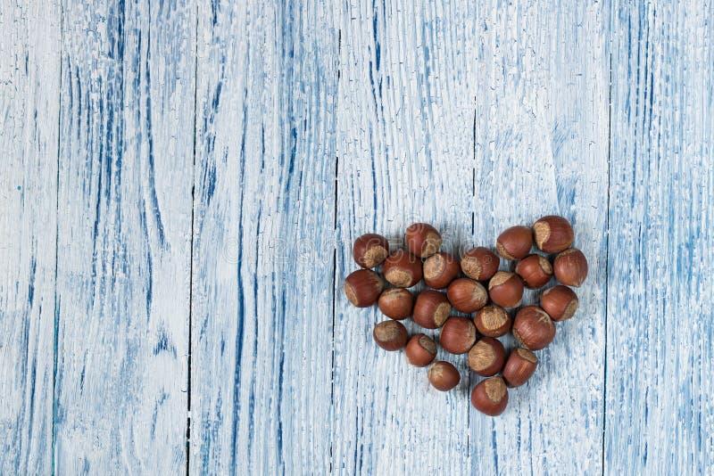 榛子心脏蓝色和whie老难看的东西木背景 图库摄影