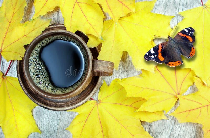 槭树和一杯咖啡黄色秋叶  复制空间 顶视图 在的海军上将蝴蝶枫叶 免版税库存图片