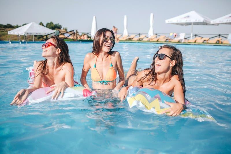 模型在游泳池变冷 性感的少妇微笑和享用 两个模型在浮游物说谎 妇女在中部 库存图片