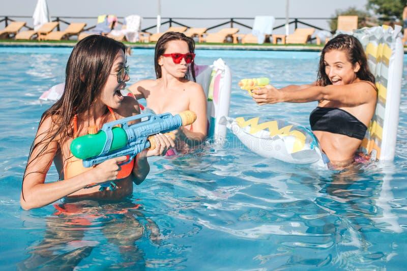 模型的图片演奏和获得乐趣在游泳池 他们有战斗 少妇射击到彼此里与 免版税库存图片