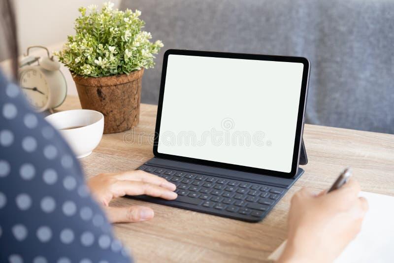 模型 亚洲女性手中的空白数字平板电脑白屏 女商人在家工作 免版税库存图片