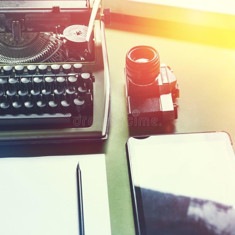 模式打字机、数字式片剂和影片照相机在选材台上,顶视图与阳光 新闻事业文字概念 库存图片