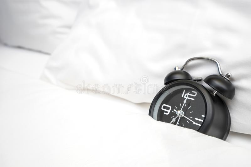 模式闹钟在白色床,时间上与明媚的阳光的早晨 免版税库存图片