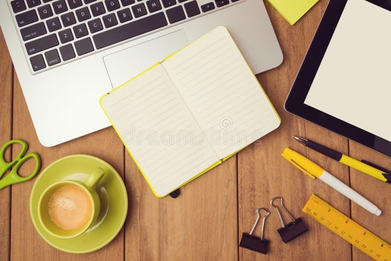 模板的办公桌嘲笑与膝上型计算机、笔记本和片剂 在视图之上 免版税图库摄影