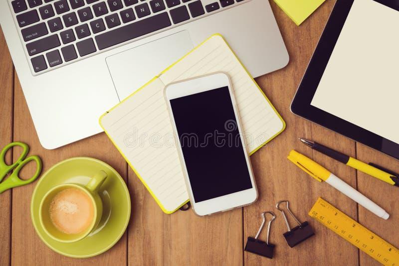 模板的办公桌嘲笑与膝上型计算机和巧妙的电话 在视图之上 免版税库存图片