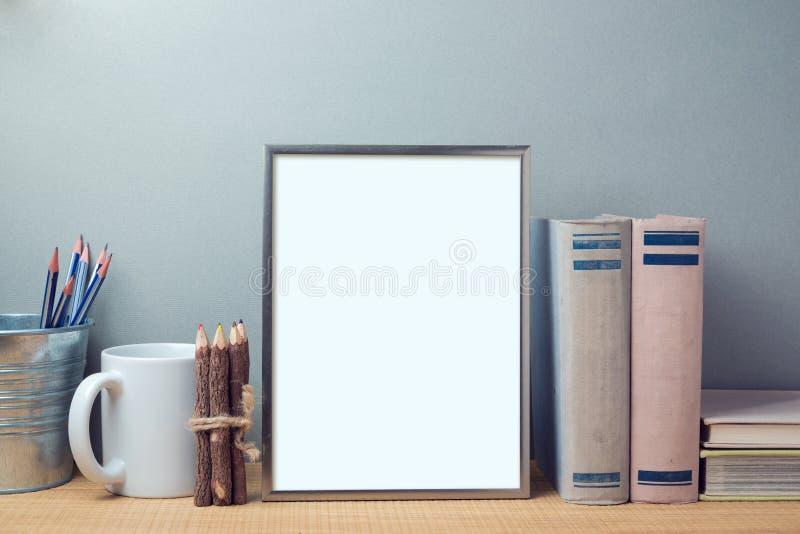 模板的海报嘲笑与书和书桌反对 免版税图库摄影