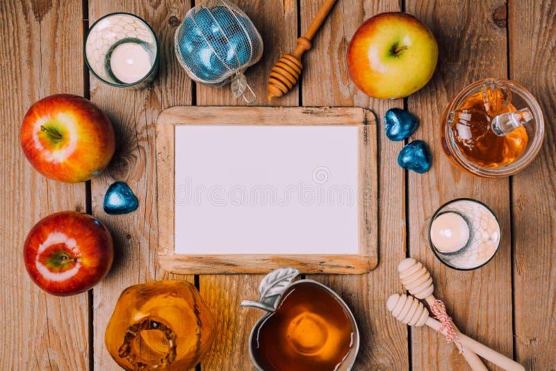 模板的犹太假日Rosh Hashana海报嘲笑用蜂蜜和苹果在木桌上 在视图之上 图库摄影