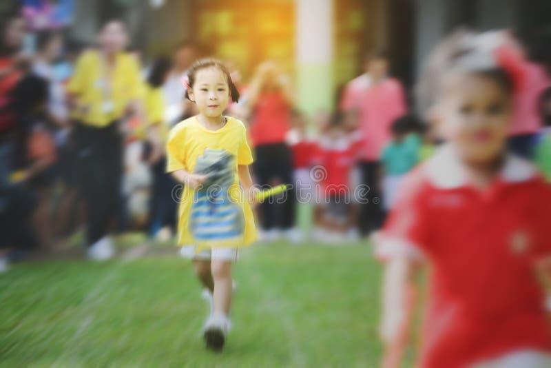 模糊的背景逗人喜爱的亚洲女孩赛跑 库存照片