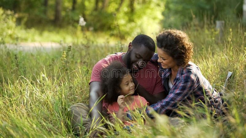 模范夫妇致力他们的时间独生子,放松在夏天公园 免版税库存照片