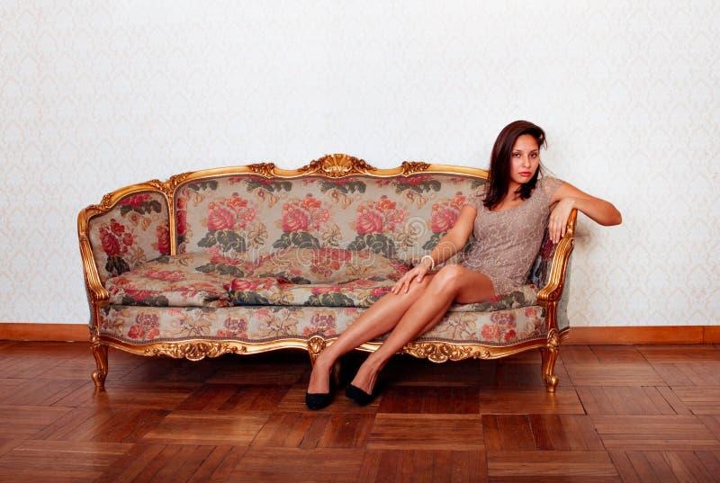 横卧在沙发的性感的西班牙妇女 免版税库存图片