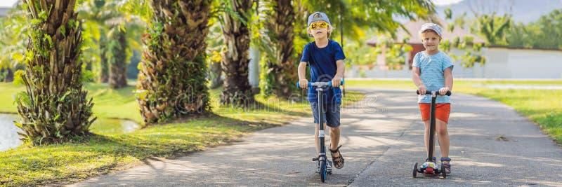 横幅、长的格式男孩和女孩反撞力滑行车的在公园 E 滑冰在晴朗的小男孩 免版税库存图片