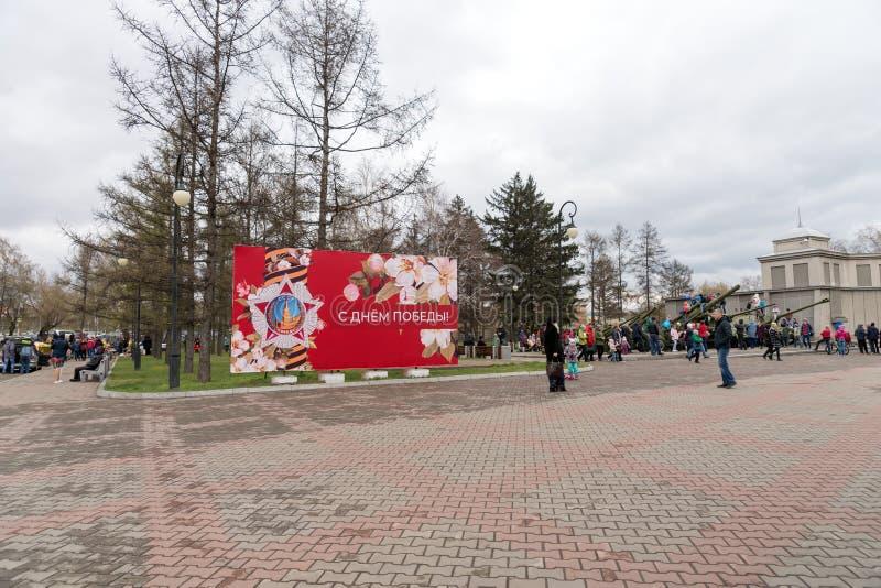 横幅与在正方形的题字愉快的胜利天在胜利纪念品的大厦博物馆附近在庆祝时 免版税库存图片