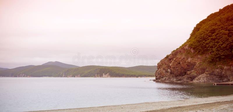 横幅海景早晨黎明天际沿海海湾小山海小卵石秋天 免版税图库摄影