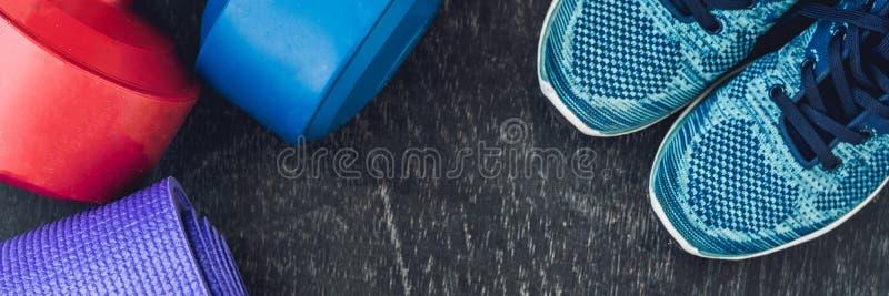 横幅瑜伽席子、体育鞋子、哑铃和瓶在蓝色背景的水 概念健康生活方式、体育和饮食 体育e 免版税库存图片