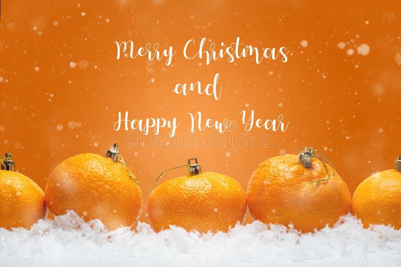 横幅用以毛皮树玩具的形式蜜桔在雪,与落的雪 与愉快的题字的橙色背景 免版税库存照片