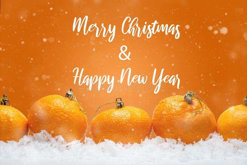 横幅用以毛皮树玩具的形式蜜桔在雪,与落的雪 与愉快的题字的橙色背景 库存照片