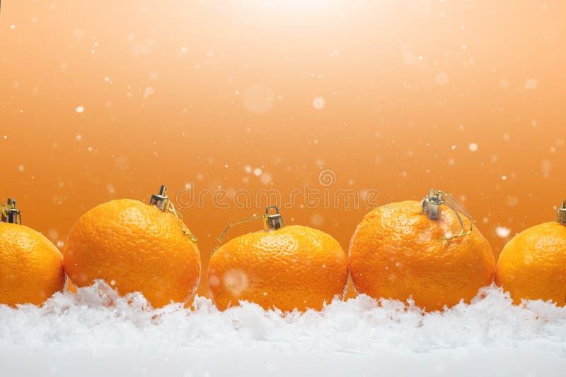 横幅用以毛皮树玩具的形式蜜桔在雪,与落的雪 圣诞节快乐或新年快乐,桔子 免版税库存照片
