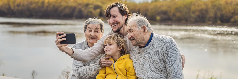 横幅,长的格式资深加上与孙子和重孙子在秋天公园采取一selfie ?? 库存照片