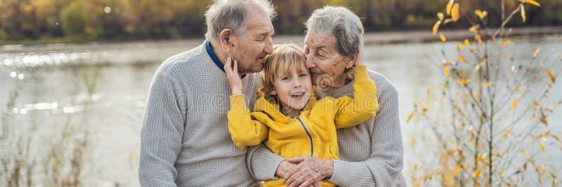 横幅,长的格式资深加上小孙子在秋天公园 曾祖母,曾祖父和伟大 库存照片