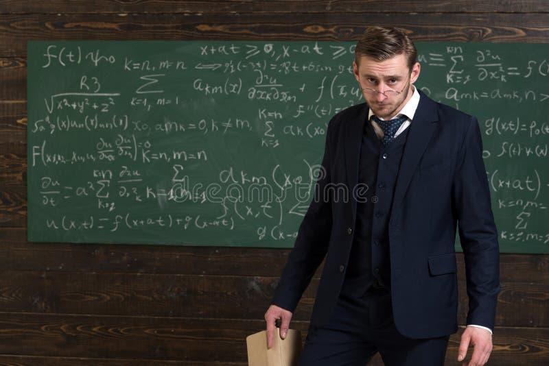 横征暴敛的老师 老师礼服和聪明玻璃的看起来,黑板背景 严密的教授横征暴敛和 免版税图库摄影