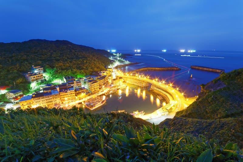 横渡一个渔村的港口的有渔船光的沿海高速公路风景在海的 免版税库存图片