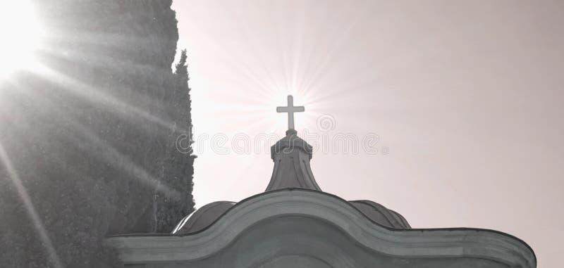 横渡在教堂的上面在有太阳光芒的公墓 库存图片