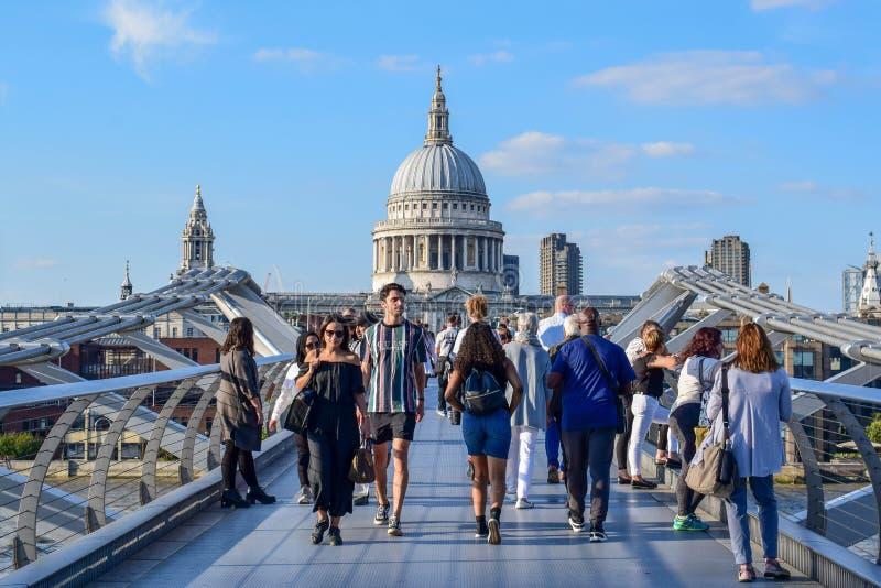 横渡在泰晤士河的人们千禧桥在伦敦,英国 库存照片