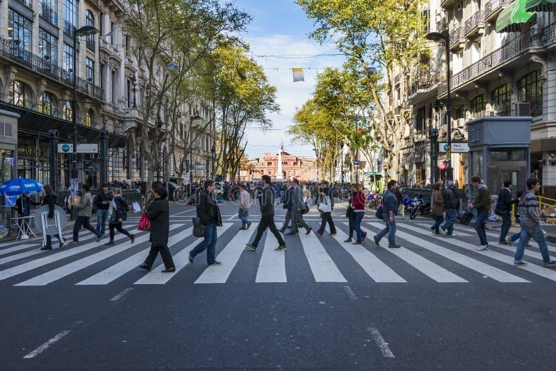 横渡在Avenida de马约角的人们一条行人交叉路在布宜诺斯艾利斯 库存照片