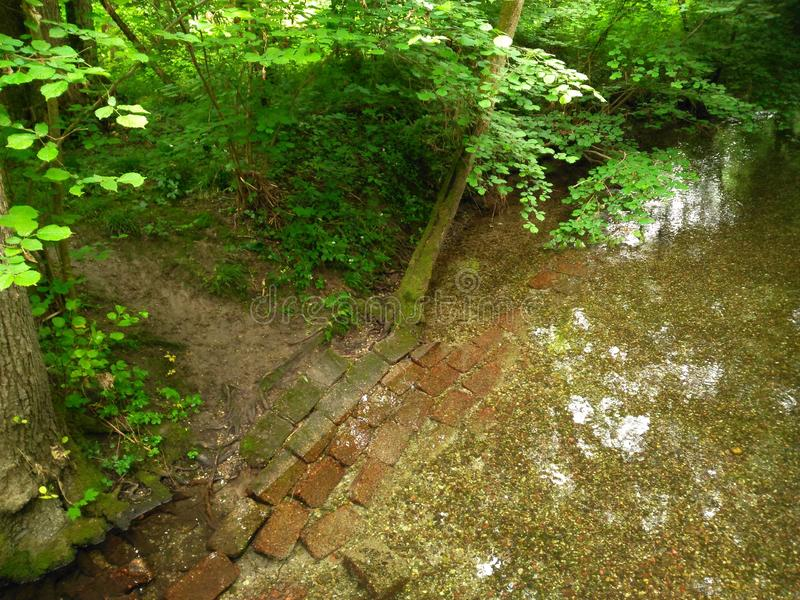 横渡小河的道路在一个进光孔礼物下 图库摄影