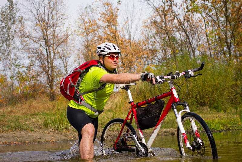 横渡有自行车的年轻运动员岩石地形在他的手上 库存照片