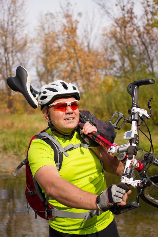 横渡有自行车的年轻运动员岩石地形在他的手上 库存图片